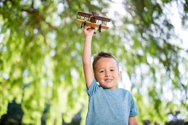 Ritratto del ragazzo che gioca con un aeroplano del giocattolo in parco
