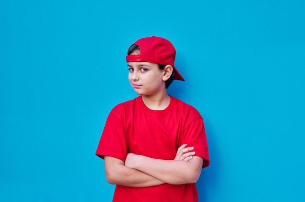 Un ritratto di ragazzo in berretto rosso e t-shirt con faccia ribelle