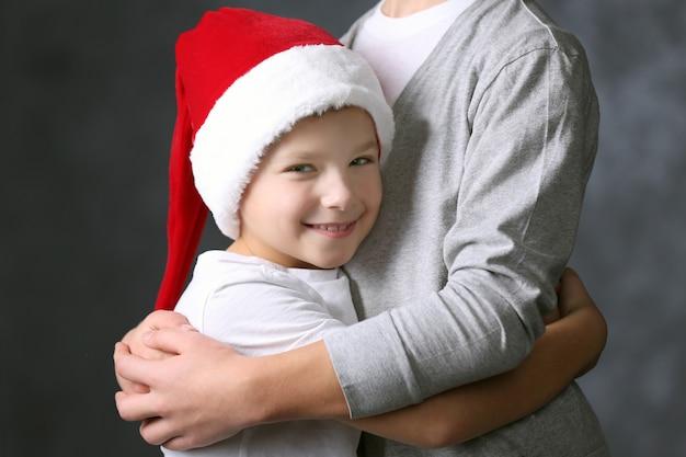Ritratto di ragazzo con cappello da babbo natale su sfondo grigio, primo piano