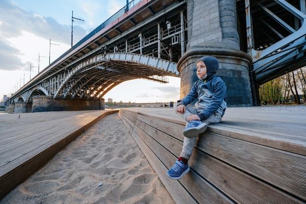Ritratto di un ragazzo seduto sulla spiaggia vicino al ponte