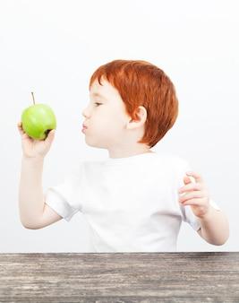 Ritratto di un ragazzo che studia e guarda una mela verde, su sfondo chiaro