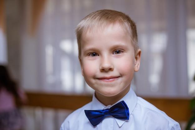 Ritratto di un ragazzo in camicia bianca e farfallino nero