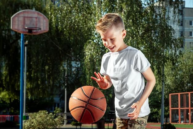 Ritratto di un ragazzo con una pallacanestro su un campo da pallacanestro