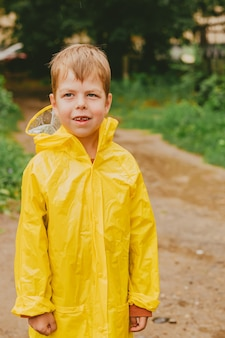 Ritratto di un ragazzo in un impermeabile giallo per strada. un bambino solo perso per strada. bambini senza supervisione. vestiti luminosi per bambini per una passeggiata