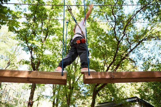 Ritratto di bambina coraggiosa a piedi su un ponte di corda in un parco avventura corda. divertirsi al parco avventura. scout che pratica la discesa in corda doppia