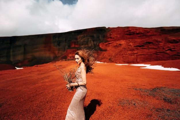 Ritratto di un modello di sposa in un abito da sera di nozze d'oro in una cava di sabbia gialla