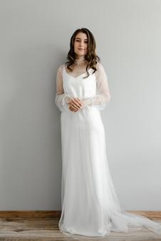 Ritratto della sposa in un abito da sposa bianco e leggero su un'uniforme elegante