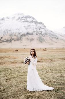 Ritratto di una sposa in abito da sposa bianco con un bouquet di spose tra le mani in un campo
