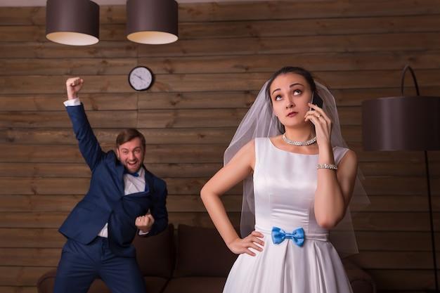 Ritratto della sposa con il telefono cellulare contro lo sposo felice sulla stanza di legno