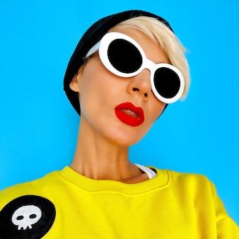 Ritratto bright hipster tom boy girl in accessori alla moda beanie e occhiali. look urbano