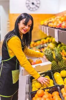 Ritratto di ragazza bruna frutta lavorando ordinare frutti in uno stabilimento di fruttivendolo