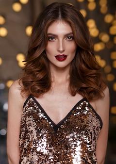 Ritratto di una ragazza bruna che indossa abiti splendenti, su uno sfondo glitterato Foto Premium
