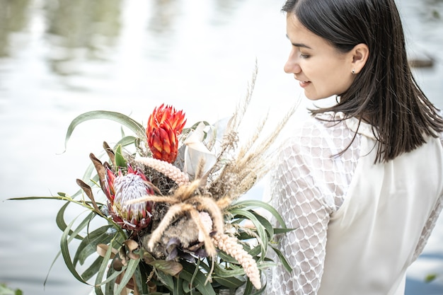 Ritratto di una ragazza bruna in abito bianco si siede in riva al fiume con un mazzo di fiori esotici, sfondo sfocato.