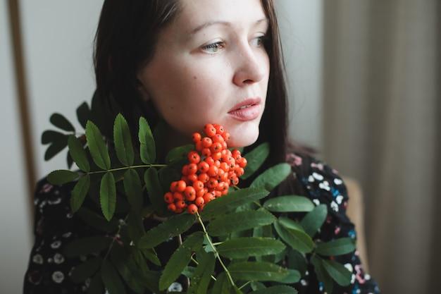 Ritratto di una ragazza bruna con fiore di sorbo