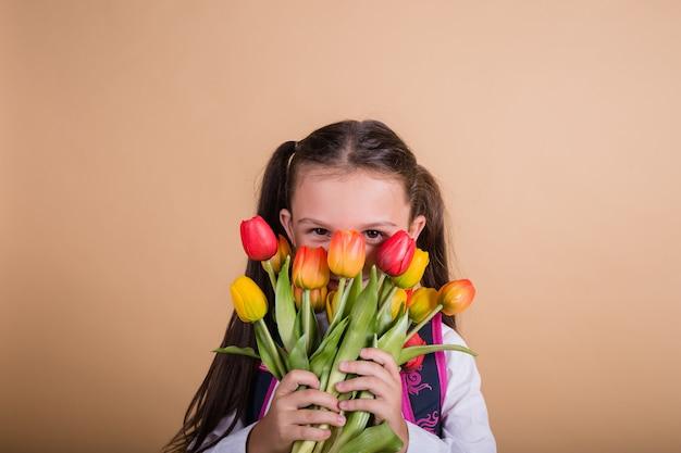 Ritratto di una studentessa bruna in uniforme che tiene un mazzo di tulipani multicolori su uno sfondo beige con un posto per il testo