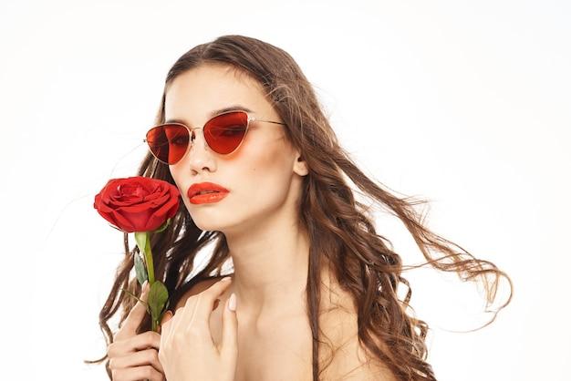 Ritratto di una bruna con rossetto rosso sulle labbra, bella donna con gli occhiali con una rosa