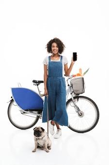 Ritratto di donna bruna che tiene lo smartphone in piedi con il suo carlino e la bicicletta isolate su un muro bianco