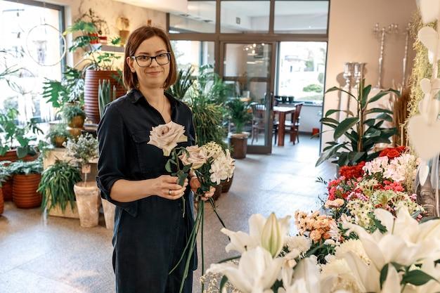 Ritratto di donna bruna con caschetto e occhiali nel suo negozio di fiori. concetto di piccola impresa e hobby.