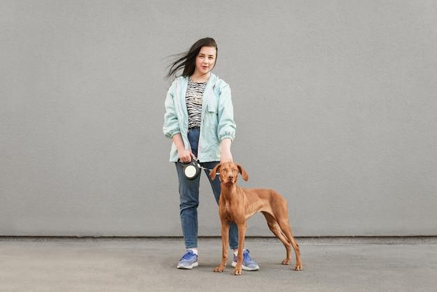 Ritratto di una donna bruna con un cane al guinzaglio si leva in piedi