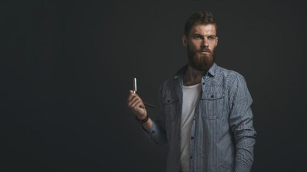 Ritratto di uomo barbuto brutale con rasoio in mano. copia spazio a sinistra