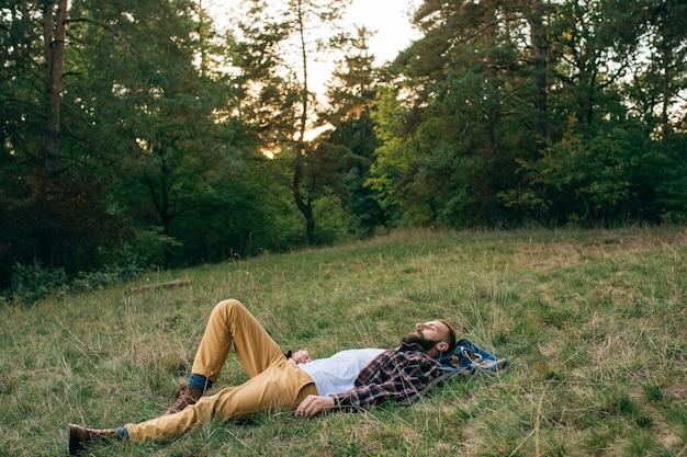 Ritratto brutale barbuto e baffuto taglialegna hipster uomo zingaro nella foresta con l'ascia. uomo disteso sull'erba e sogni