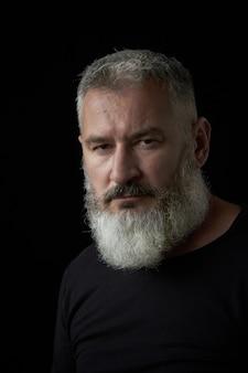 Ritratto di un uomo dai capelli grigio brutale con una barba lussureggiante grigia e una faccia severa su sfondo nero, messa a fuoco selettiva
