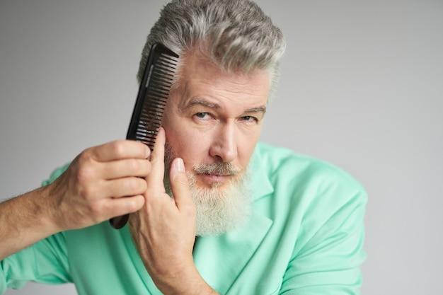 Ritratto di brutale uomo di mezza età con la barba che guarda la telecamera mentre si spazzola i capelli con