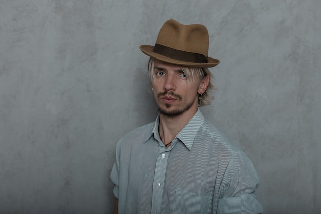 Ritratto di un giovane brutale in elegante cappello marrone in camicia elegante classica al chiuso vicino a un muro vintage. modello di ragazzo attraente è in piedi nella stanza. abbigliamento da uomo alla moda. stile retrò.