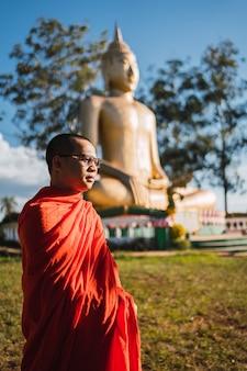 Ritratto di un monaco buddista, sullo sfondo l'immagine del buddha più grande del sud america