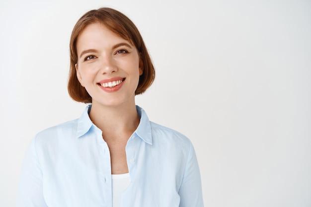 Ritratto di donna d'affari in camicetta blu, sorridente con i denti bianchi, dall'aspetto professionale. lavoratrice imprenditrice in piedi contro il muro bianco