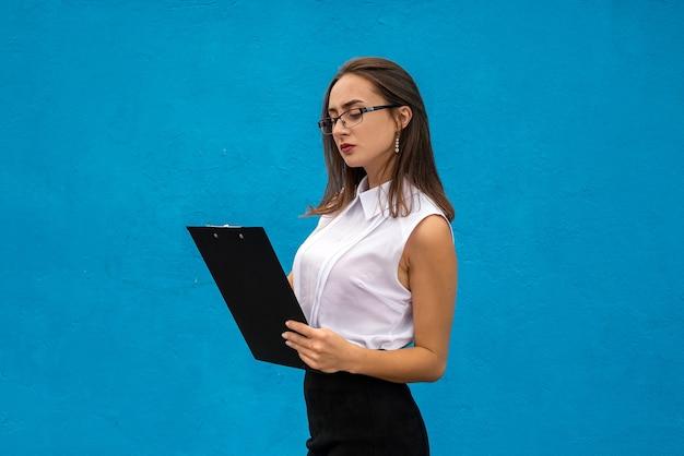 Il ritratto della signora di affari scrive sulla lavagna per appunti isolata sull'azzurro. concetto di occupazione o lavoro