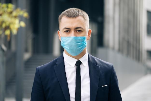 Ritratto di uomo d'affari in maschera protettiva guarda l'infezione da coronavirus covid-19 della fotocamera