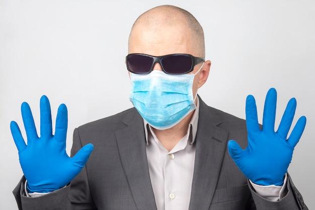 Ritratto di un uomo d'affari in occhiali da sole, una mascherina medica e guanti protettivi