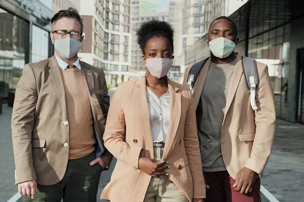 Ritratto di uomini d'affari in maschere protettive guardando la fotocamera mentre si trovava in città