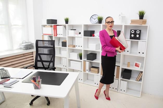 Ritratto di una ragazza in stile business alla ricerca di documenti in una cartella rossa. giornata lavorativa in ufficio