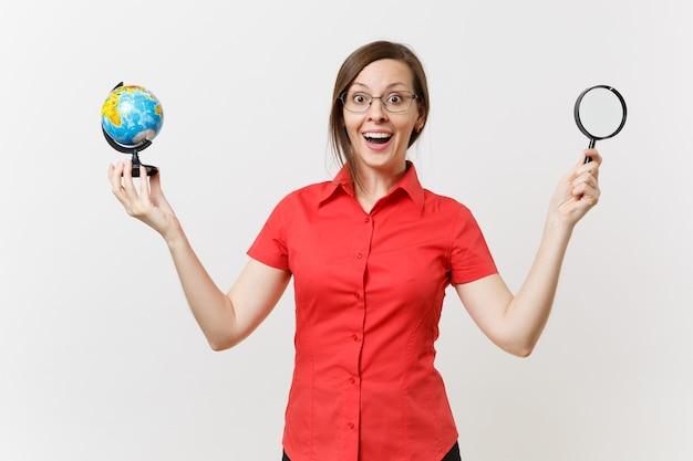 Ritratto della donna dell'insegnante di affari in camicia rossa che tiene e che guarda tramite la lente d'ingrandimento sul globo isolato su fondo bianco. insegnamento dell'istruzione nel concetto di università delle scuole superiori. copia spazio.