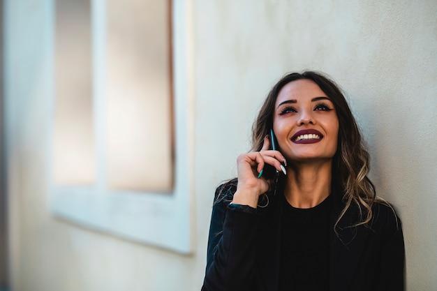 Ritratto di donna d'affari all'aperto con il cellulare. primo piano della ragazza castana