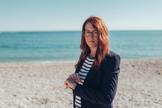 Ritratto di una donna d'affari sorridente che controlla smartwatch in riva al mare