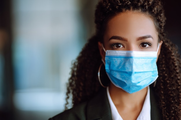Ritratto di una donna d'affari che indossa una maschera protettiva e guarda a porte chiuse.
