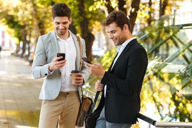 Ritratto di uomini d'affari in giacca e cravatta utilizzando smartphone mentre si cammina all'aperto attraverso il parco verde con caffè da asporto, durante la giornata di sole