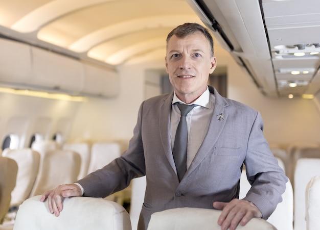 Ritratto di uomo d'affari su un aereo, passeggero rilassante