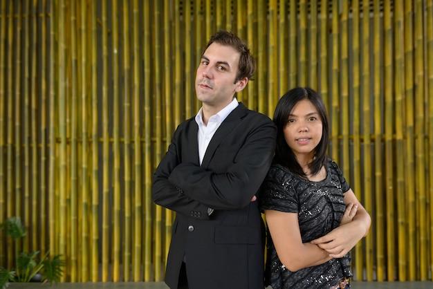 Ritratto di uomo d'affari e imprenditrice asiatica come coppia multietnica insieme contro il muro di bambù all'aperto