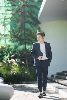 Ritratto dell'uomo d'affari che tiene compressa digitale, concetto di affari