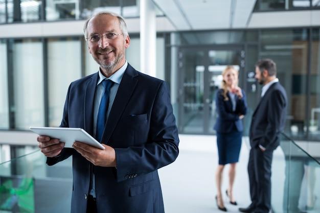 Ritratto dell'uomo d'affari che tiene compressa digitale e colleghi che parlano nel fondo