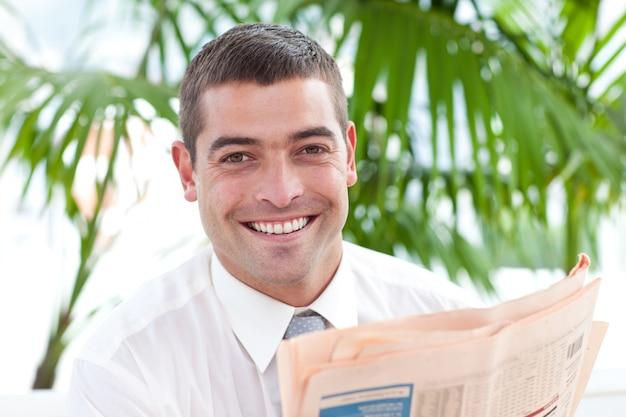 Ritratto di un uomo d'affari che legge un giornale sul posto di lavoro