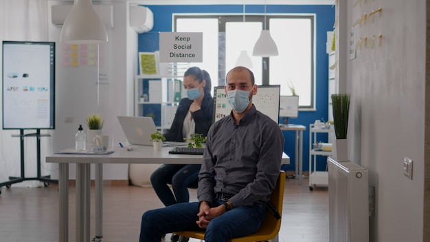 Ritratto di uomo d'affari seduto alla scrivania dell'ufficio che indossa una maschera medica contro l'infezione da coronavirus durante la pandemia globale. i lavoratori di squadra che lavorano al progetto aziendale mantengono il distanziamento sociale