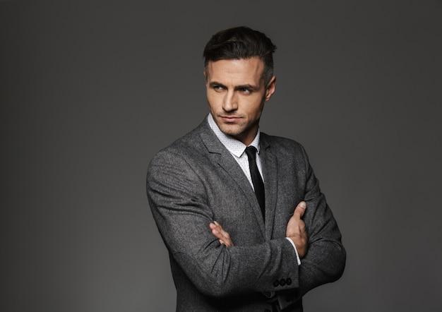 Ritratto di uomo d'affari che indossa il costume formale in piedi con le braccia incrociate e guardando da parte, isolato sopra il muro grigio