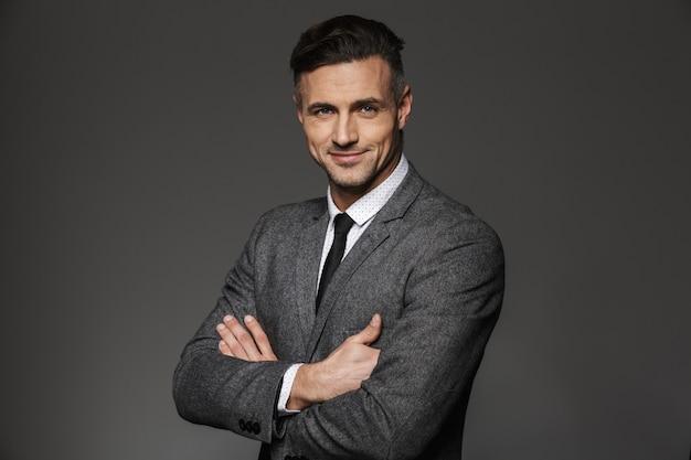 Ritratto di uomo d'affari che indossa il costume formale in piedi con le braccia conserte e sorridente, isolato sopra il muro grigio