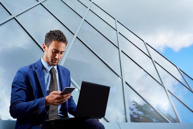 Ritratto dell'uomo d'affari con il computer portatile che parla sul concetto di affari del telefono cellulare
