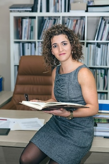 Ritratto di donna d'affari in possesso di notebook seduto sul tavolo desktop in ufficio e guardando la fotocamera